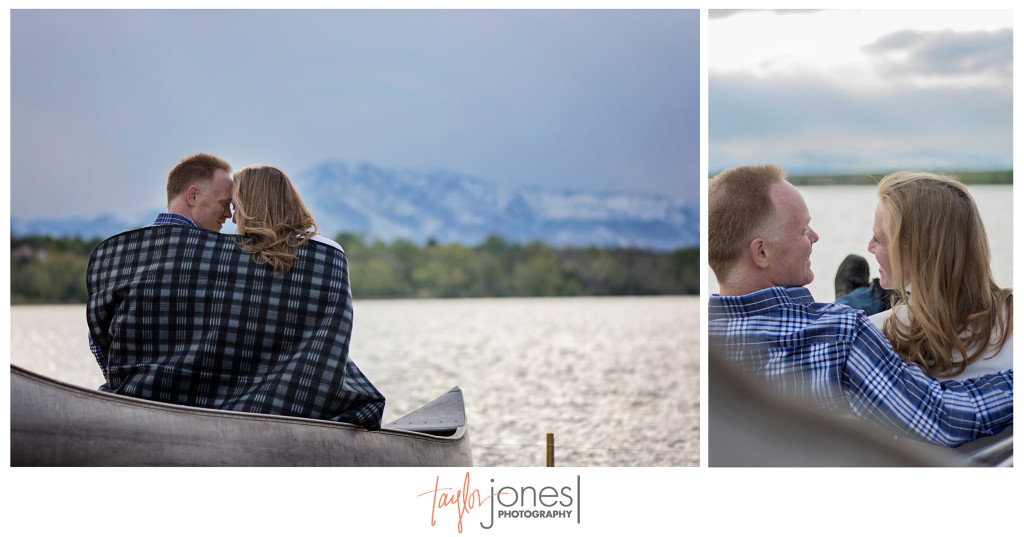 Couple sitting in a canoe on a pond at their engagement shoot with the Rocky Mountains in the background at sunset.