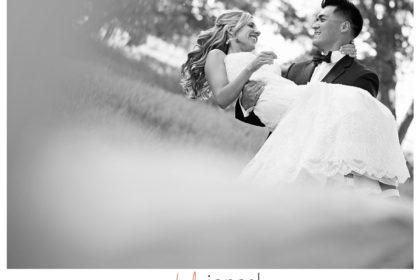 Groom carrying bride at their wedding at Arrowhead Golf Club