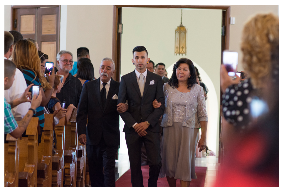 Groom with parents walking down aisle