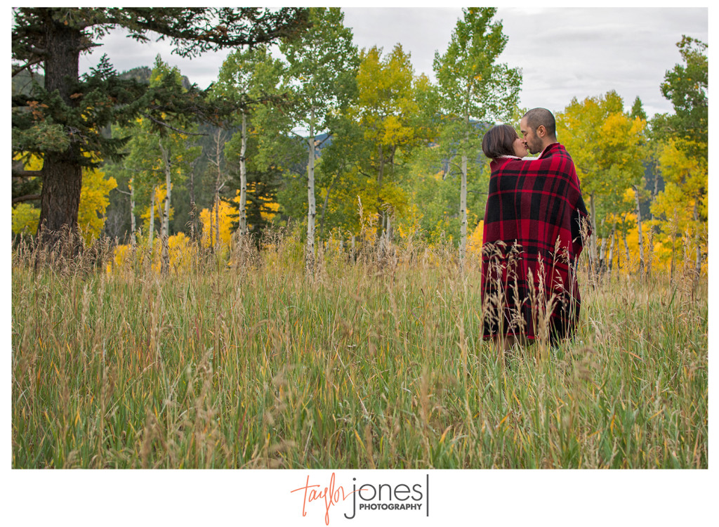 Couple standing in a field with aspens and a plaid blanket in Golden Colorado