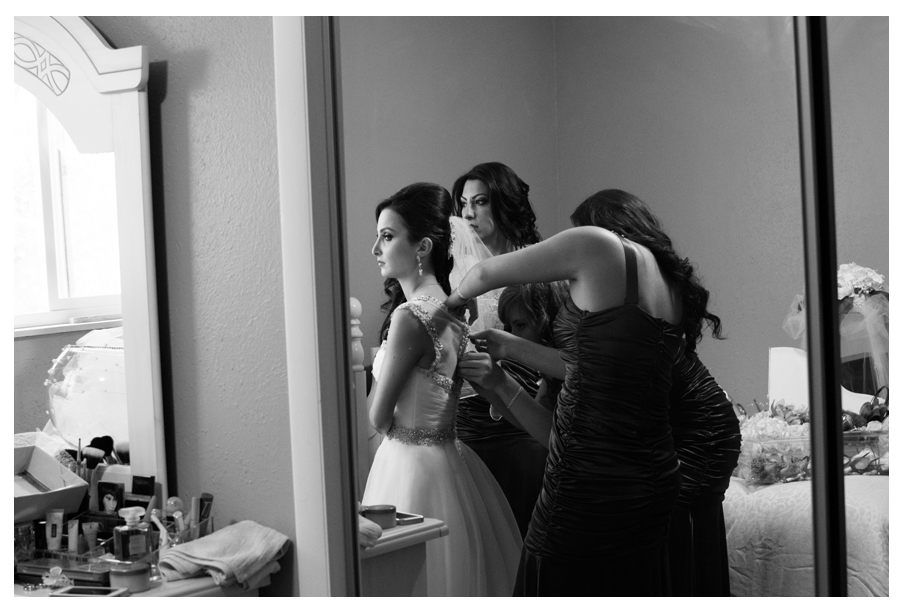 Bride at her home in childhood bedroom with her bridesmaids putting her dress on