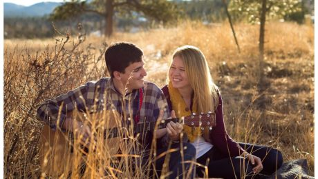Couple sitting in a field playing guitar