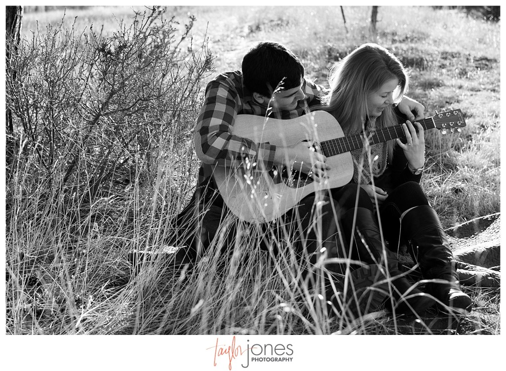 Couple at engagement shoot kissing with guitar