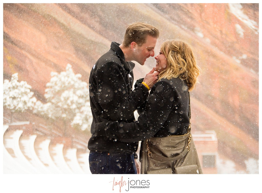 Couple kissing at Red Rocks winter proposal