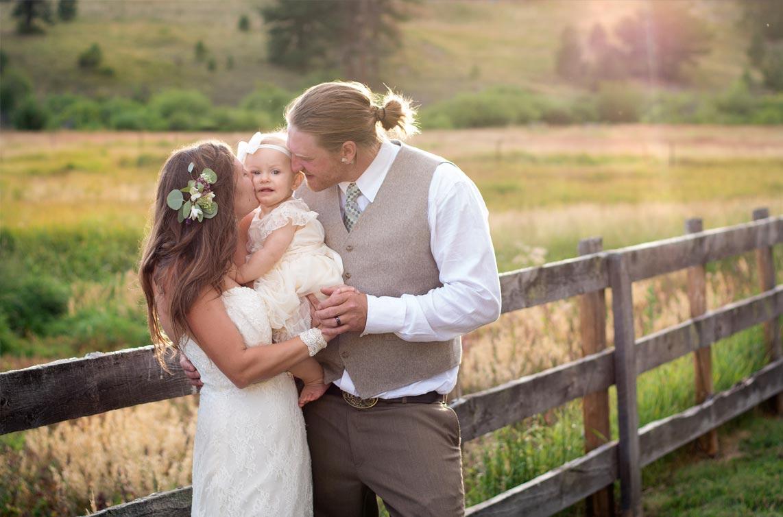 Bride and groom with daughter at Deer Creek Valley Ranch Bailey Colorado wedding