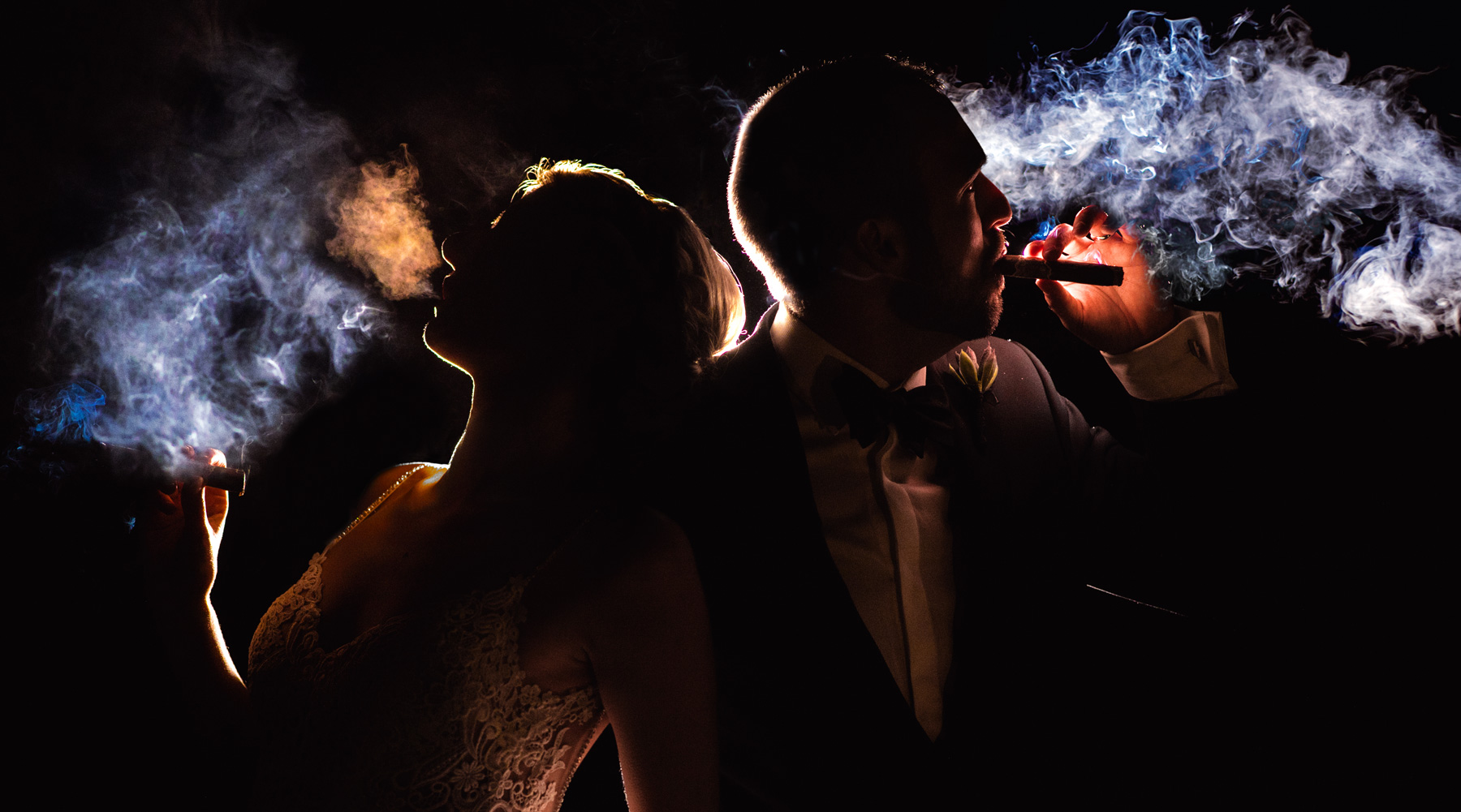 Bride and groom smoking cigar at wedding with off camera flash magnet modification
