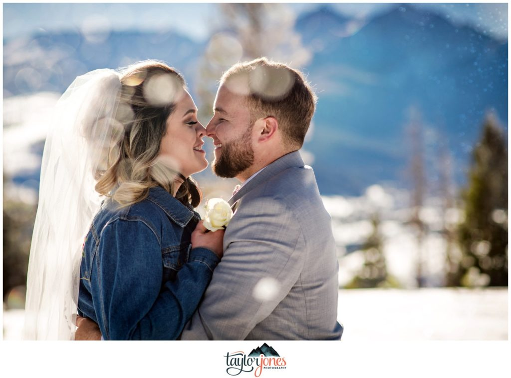 Bride and groom kissing in snow at Sapphire Point elopement